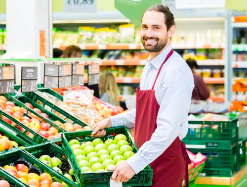 Supermarket clerk filling up apple storage racks in fruit department